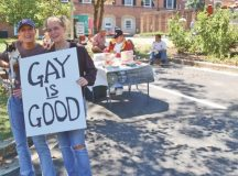 """IN JUXTAPOSITION at the Falls Church Fall Festival Saturday, Rachel Kirk and Katie Demente holding a sign used by the Parents and Friends of Lesbians and Gays (PFLAG) reading """"Gay Is Good,"""" next to Greg Quinlan at a table for Parents and Friends of Ex-Gays (PFOX), which represented the opposite point of view. (News-Press photo)"""